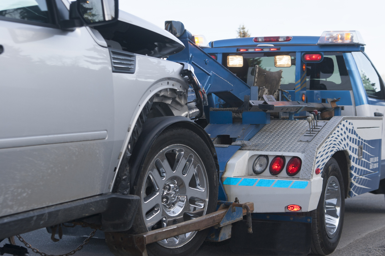 A damaged new vehicle on a tow truck. Medium shot.